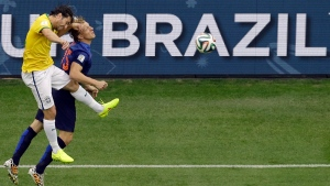 Brazil's Maxwell, left, and Netherlands' Dirk Kuyt go for a header during the World Cup third-place soccer match between Brazil and the Netherlands at the Estadio Nacional in Brasilia, Brazil, Saturday, July 12, 2014. (AP / Themba Hadebe)