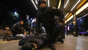 Police officers detain several men after riot police fired tear gas and used water cannons to restrain a group of youths who hurled rocks and vandalized store fronts at a rally to celebrate Argentina's gutsy performance in a 1-0 loss to Germany in the World Cup finals, in Buenos Aires, Argentina, Sunday, July 13, 2014. (AP / Jorge Saenz)