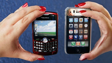 A customer holds up her Apple iPhone, right, which is shown next to a Blackberry Curve, left, at a Best Buy in Mountain View, Calif. (AP / Paul Sakuma)