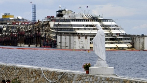 A statue of the Madonna stands at the port of the Tuscan island of Giglio, Italy, as operations to refloat and tow away the luxury cruise ship Costa Concordia get underway, Monday, July 14, 2014. (AP / Giacomo Aprili)