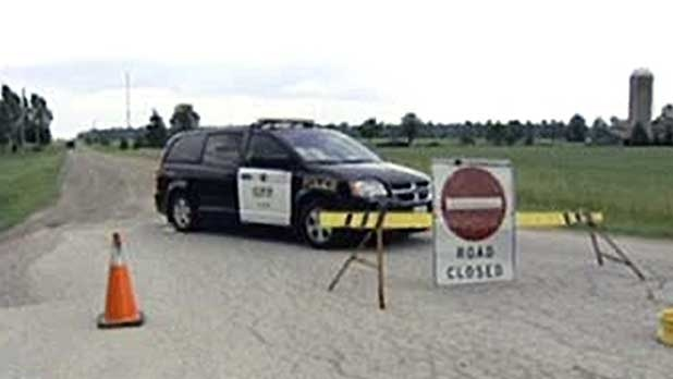 An OPP vehicle blocks Arkona Road near a home where the body of a woman was found in Lambton County, Ont. on Monday, July 14, 2014. (Steve Ward / CTV London)