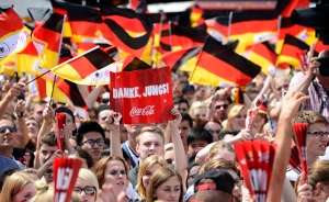 A man holds a sign that says 'Thanks boys' as several hundred thousand people wait for the arrival of the German national soccer team on the stage at Brandenburg gate in Berlin Tuesday, July 15, 2014. (AP / Jens Meyer)