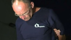 Calgary Police lead Douglas Garland into the arrest processing unit on July 14, 2014.