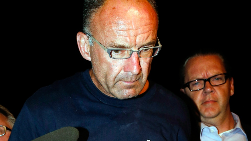 Douglas Garland is escorted into a Calgary police station, late Monday, July 14, 2014. (Jeff McIntosh / THE CANADIAN PRESS)