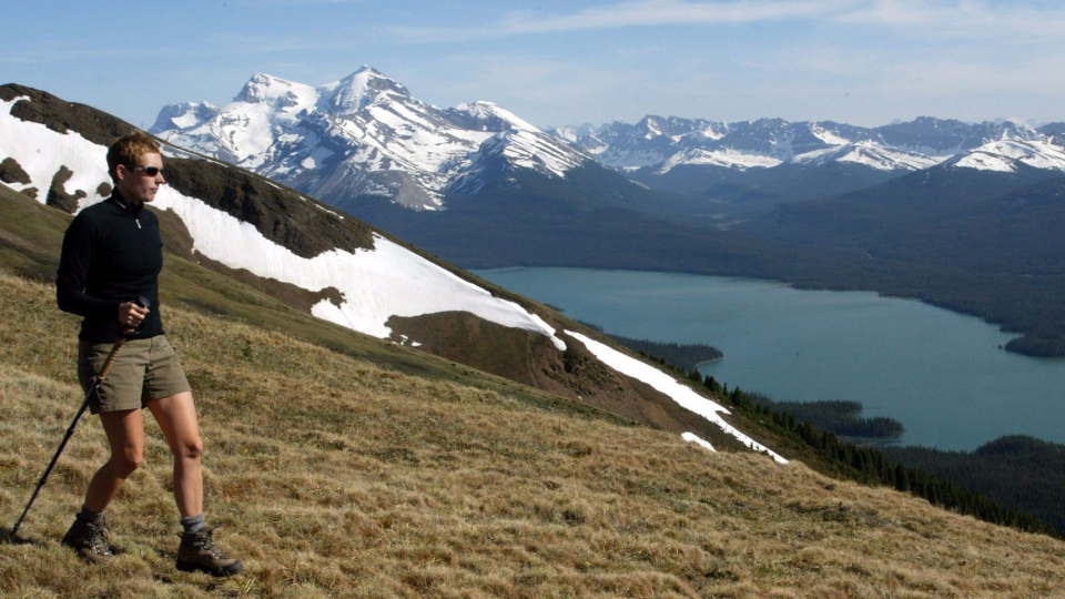 In this June 2002 file photo, a hiker takes in the snow-covered mountains surrounding Maligne Lake in Jasper National Park. (Jonathan Hayward / THE CANADIAN PRESS)