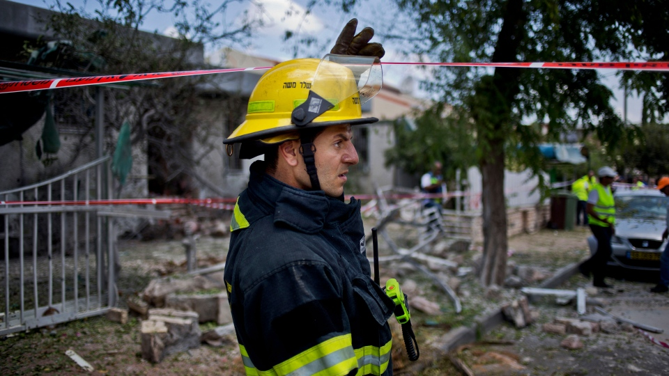 An Israeli firefighter inspects the site after a rocket fired by militants hit Ashdod, Israel, Tuesday, July 15, 2014. (AP / Ariel Schalit)