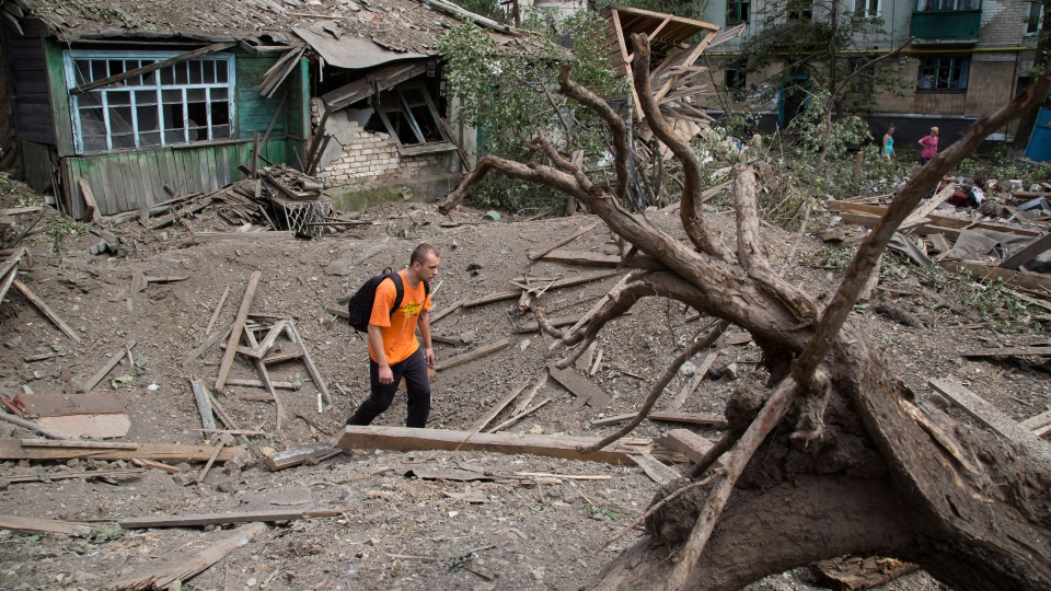 A man walks in a bomb crater near a damaged private house after an airstrike in Snizhne, 100 kms east from the city of Donetsk, easternUkraine Tuesday, July 15, 2014. (AP / Dmitry Lovetsky)
