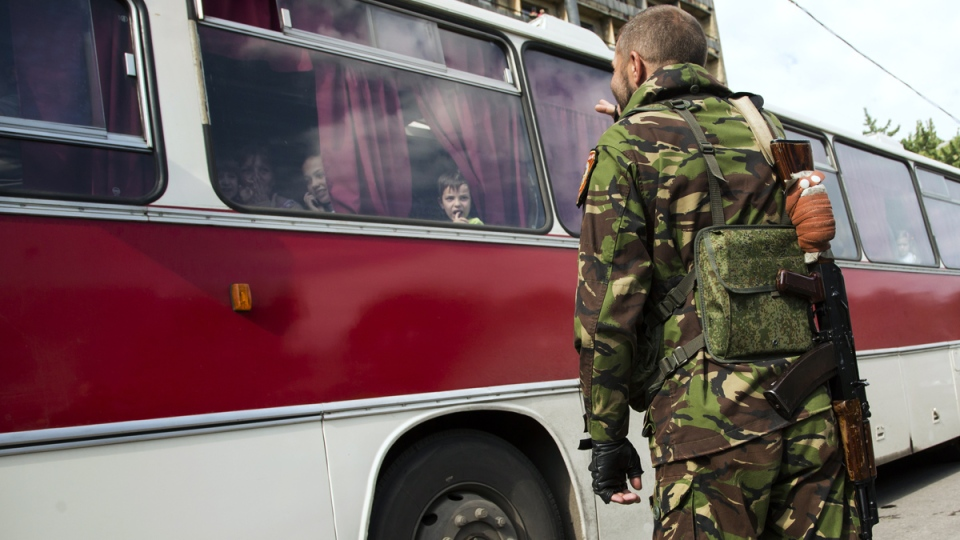 A Donetsk People's Republic fighter says goodbye to his family who are departing as refugees to Russia in the city of Donetsk, eastern Ukraine, Wednesday, July 16, 2014. (AP / Dmitry Lovetsky)