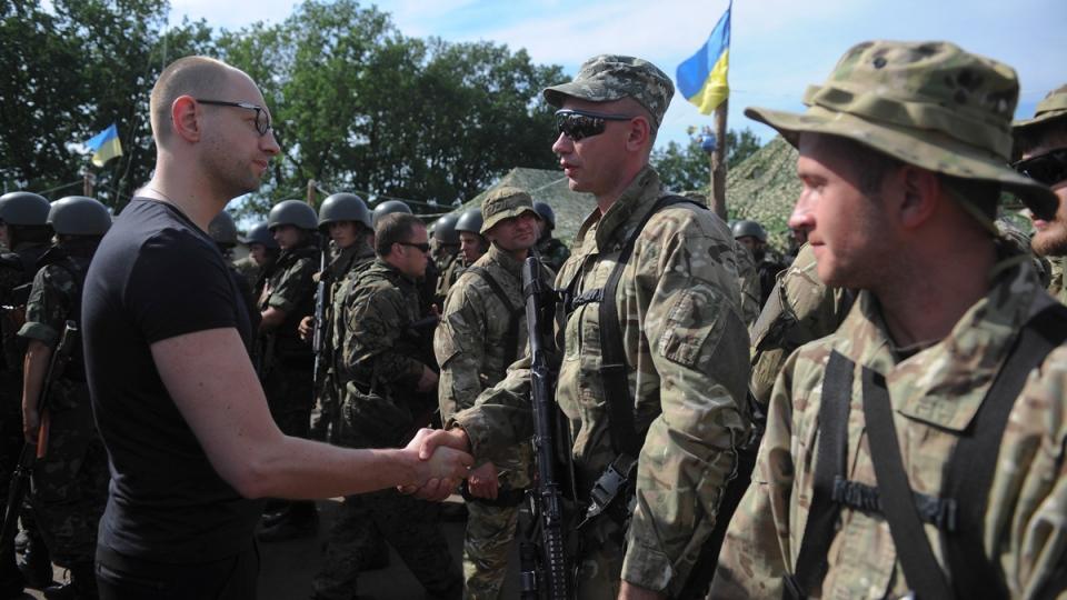 Ukrainian Prime Minister Arseniy Yatsenyuk, left, greets a soldier during inspection of a Ukrainian Army position outside the eastern town of Slovyansk, Ukraine, Wednesday, July 16, 2014. (AP / Andrew Kravchenko)