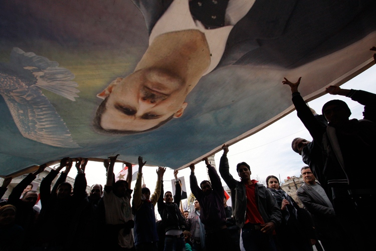 Supporters of Syrian President Bashar Assad hold a large banner bearing his likeness during a rally in Damascus, Syria, Friday, Dec. 30, 2011. (AP / Muzaffar Salman)