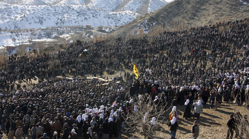 In this Friday, Dec. 30, 2011 photo, thousands of mourners gathered around coffins on a hillside in Gulyazi village, on the border with Iraq, southeast Turkey, for the funerals of 35 Kurdish civilians who were killed in a botched raid by Turkish military jets that mistook the group for Kurdish rebels based in Iraq. (AP Photo)