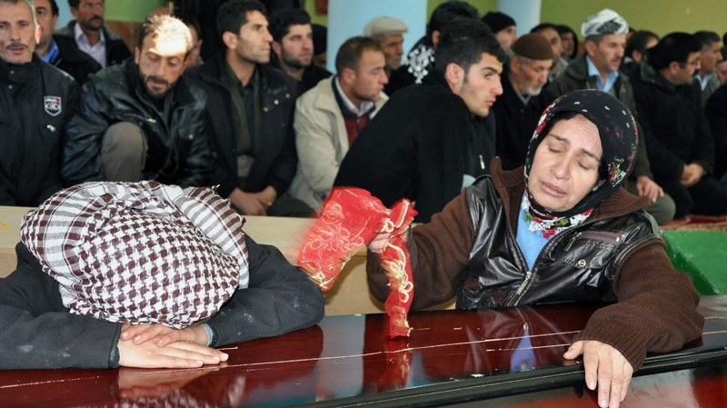 In this Friday, Dec. 30, 2011 photo, women cry over the coffins of victims in a mosque as thousands of mourners gathered in Gulyazi village at the border with Iraq, southeast Turkey, for the funerals of 35 Kurdish civilians who were killed in a botched raid by Turkish military jets that mistook the group for Kurdish rebels based in Iraq.