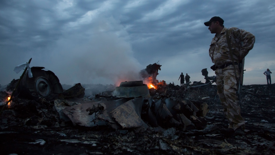 People walk amongst the debris, at the crash site of a passenger plane near the village of Grabovo, Ukraine, Thursday, July 17, 2014. (AP / Dmitry Lovetsky)