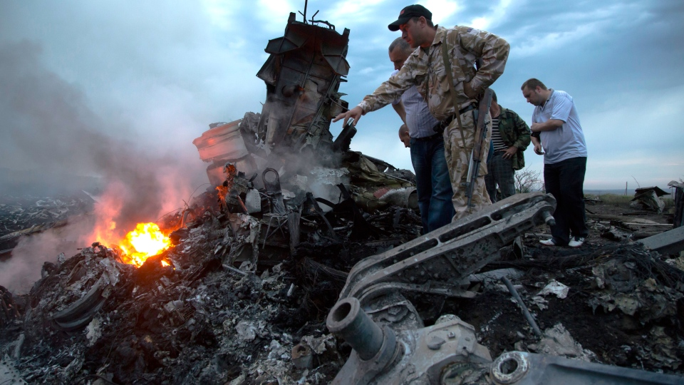 People inspect the crash site of a passenger plane near the village of Grabovo, Ukraine, Thursday, July 17, 2014. (AP / Dmitry Lovetsky)