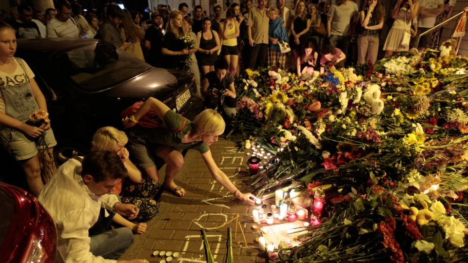 People hold candles and place flower tributes placed outside the Dutch embassy to commemorate victims of Malaysia Airlines plane crash in Kyiv, Ukraine, Thursday, July 17, 2014. (AP / Sergei Chuzavkov)