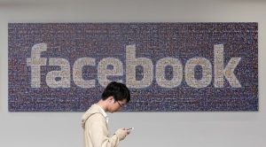 A man walks past a Facebook sign in an office on the Facebook campus in Menlo Park, Calif on June 11, 2014. (AP/Jeff Chiu)