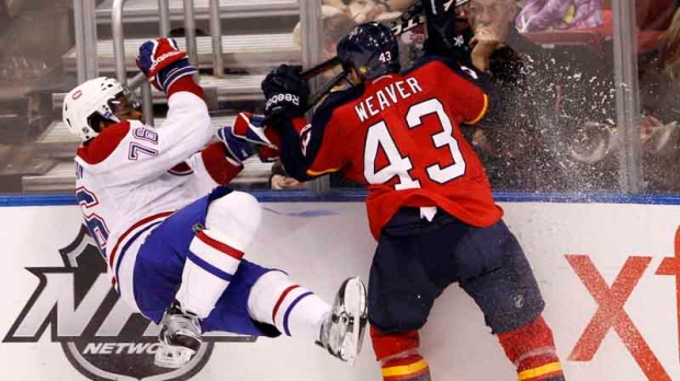 Florida Panthers defenseman Mike Weaver (43) checks Montreal Canadiens defenseman P.K. Subban (76) into the boards during the third period of an NHL hockey game, Saturday, Dec. 31, 2011, in Sunrise, Fla. The Panthers defeated the Canadiens 3-2. (AP Photo/Wilfredo Lee)