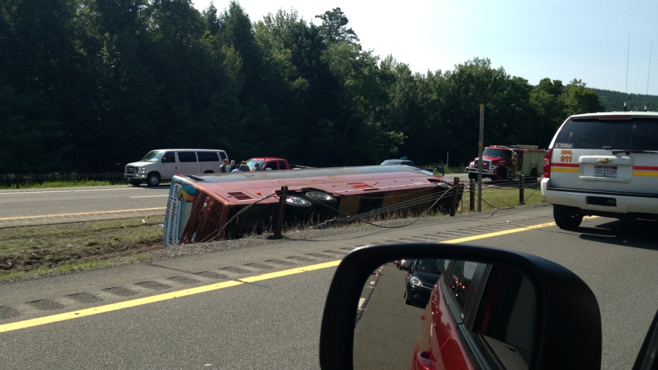 A Canadian tour bus carrying 54 people from Quebec City to New York City rests on its side after rolling over on the Northway in the Adirondacks in Essex County, N.Y., Friday, July 18, 2014. (Adirondack Daily Enterprise, Catherine Moore)