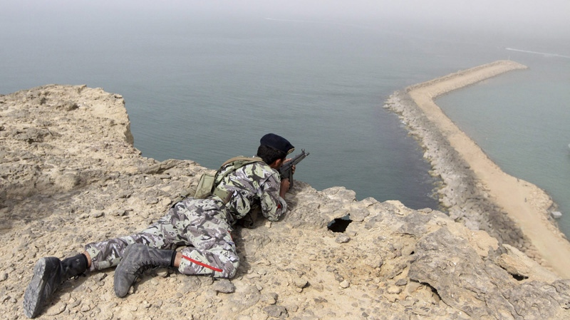 A member of the Iranian military takes position in a drill on the shore of the sea of Oman, on Friday, Dec. 30, 2011. (AP Photo/YJC, Mohammad Ali Marizad)