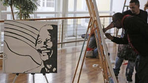 The face of former South African President Nelson Mandela is displayed as people paint during his birthday celebrations in Cape Town, South Africa, Friday, July 18, 2014. (AP / Schalk van Zuydam)