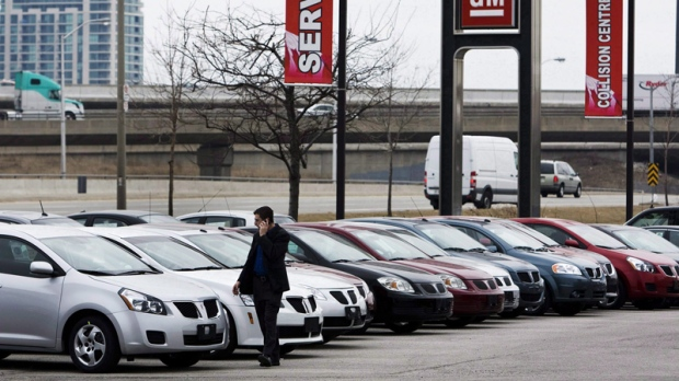 A man walks past cars at a General Motors dealership in Toronto on Thursday, March 5, 2009. THE CANADIAN PRESS/Nathan Denette