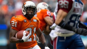 B.C. Lions' Ryan Phillips, left, runs with the ball after intercepting a Montreal Alouettes pass during second half CFL action in Vancouver, B.C., on Saturday July 19, 2014. THE CANADIAN PRESS/Darryl Dyck
