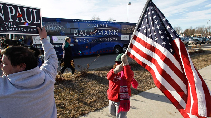 Supporters of Republican presidential, candidate Rep. Ron Paul, R-Texas, carry signs and flags near the campaign bus for fellow Republican presidential candidate Rep. Michele Bachmann, R-Minn, during a campaign stop at Valley High School in West Des Moines, Iowa, Tuesday, Jan. 3, 2012. (AP / Eric Gay)