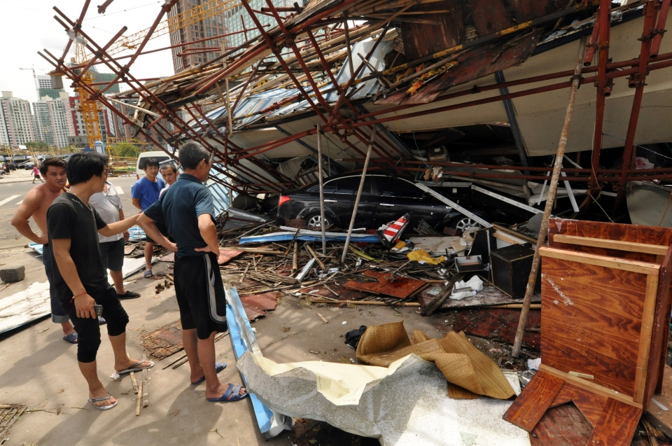 A vehicle sits under a collapsed building after landfall of typhoon Rammasun in Haikou, capital of south China's Hainan Province, Saturday, July 19, 2014. (Xinhua / Xia Yifang)