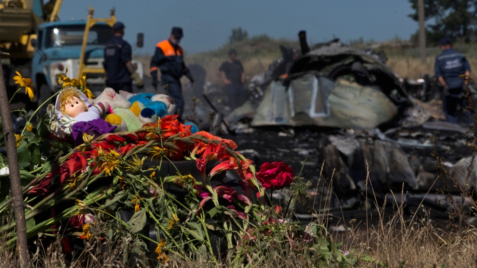 Toys and flowers are placed at the crash site of Malaysia Airlines Flight 17 near the village of Hrabove, eastern Ukraine, Donetsk region, eastern Ukraine Monday, July 21, 2014. (AP / Dmitry Lovetsky)