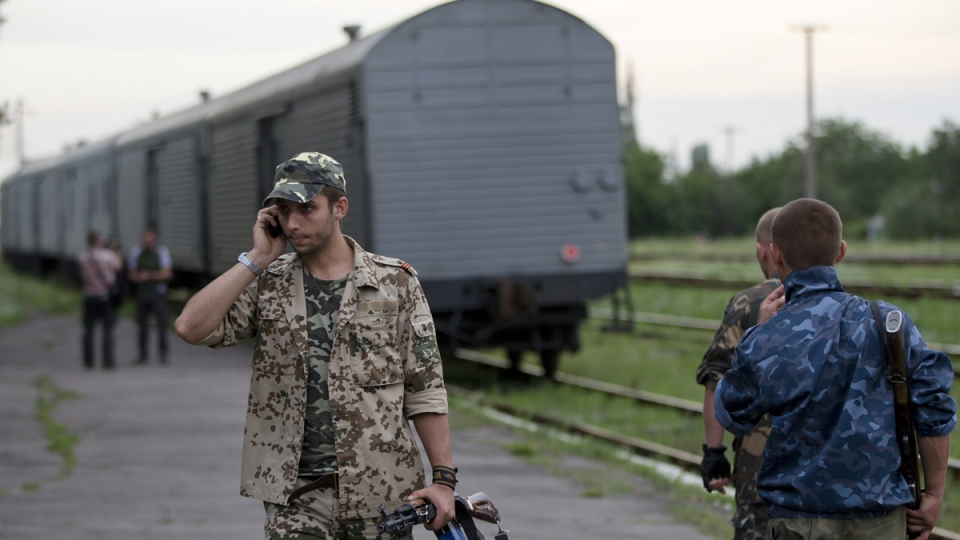 A pro-Russian rebel speaks on the phone as a refrigerated train loaded with bodies of the passengers departs the station in Torez, eastern Ukraine, 15 kilometres from the crash site of Malaysia Airlines Flight 17, Monday, July 21, 2014. (AP / Vadim Ghirda)
