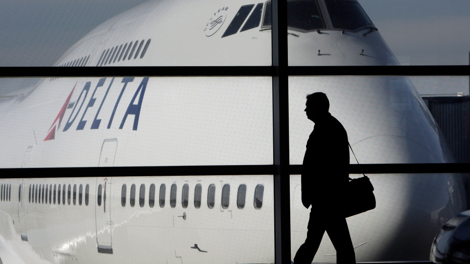 A passenger walks past a Delta Airlines 747 aircraft at Detroit Metropolitan Wayne County Airport in Romulus, Mich., on Jan. 21, 2010.  (AP / Paul Sancya)