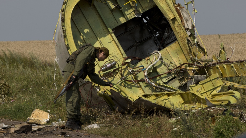 A pro-Russian rebel touches the MH17 wreckage at the crash site of Malaysia Airlines Flight 17, near the village of Hrabove, eastern Ukraine, Tuesday, July 22, 2014. (AP / Vadim Ghirda)