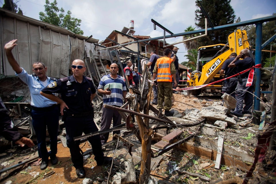Israeli police officers secure a destroyed house that was hit by a rocket fired by Palestinians militants from Gaza, in Yahud, a Tel Aviv suburb near the airport, central Israel, Tuesday, July 22, 2014. (AP / Dan Balilty)