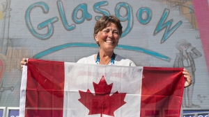 Trap shooter Susan Nattrass smiles as she displays the Canadian flag at the Commonwealth Games in Glasgow, Scotland on July 21, 2014. (THE CANADIAN PRESS / Andrew Vaughan)