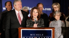 Rep. Michele Bachmann, R-Minn., center, joined by husband Marcus, left, family and friends, announces that she will end her campaign for president in West Des Moines, Iowa, Wednesday, Jan. 4, 2012. (AP / Chris Carlson)