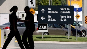 Canadian border guards are silhouetted as they replace each other at an inspection booth at the Douglas border crossing on the Canada-USA border in Surrey, B.C., on Thursday August 20, 2009. (THE CANADIAN PRESS/Darryl Dyck)