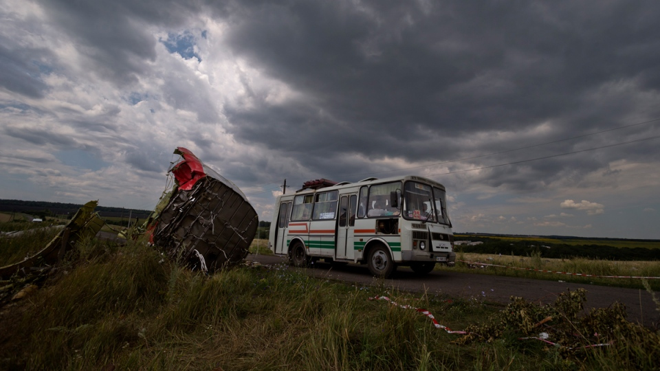 A commuter bus drives by aircraft wreckage at the crash site of Malaysia Airlines Flight 17 near the village of Hrabove, eastern Ukraine, Tuesday, July 22, 2014. (AP / Vadim Ghirda)