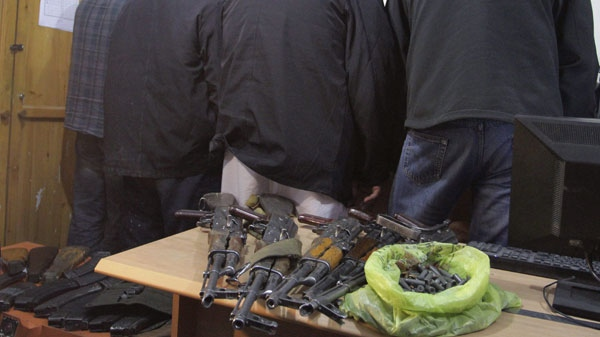 Detained members of Garda World private security company are seen near their confiscated arms during a news event in Kabul, Afghanistan, Thursday, Jan. 5, 2012.