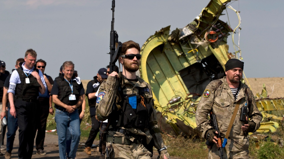 Pro-Russian rebels, right, followed by members of the OSCE mission, walk by plane wreckage as they arrive for a media briefing at the crash site of Malaysia Airlines Flight 17, near the village of Hrabove, eastern Ukraine, Tuesday, July 22, 2014. (AP / Vadim Ghirda)