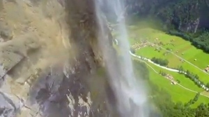 Wingsuit wearer flies through waterfall before lan