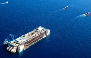 In this aerial picture provided by the Italian Civil Protection Department, the wreck of the Costa Concordia is towed by two tugboats as it leaves behind the tiny Tuscan island of Isola del Giglio, Italy, Wednesday, July 23, 2014.