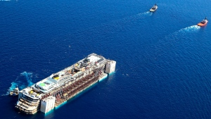 In this aerial picture provided by the Italian Civil Protection Department, the wreck of the Costa Concordia is towed by two tugboats as it leaves behind the tiny Tuscan island of Isola del Giglio, Italy, Wednesday, July 23, 2014. (Courtesy of the Italian Civil Protection Department)