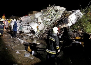 Rescue workers survey the wreckage of TransAsia Airways flight GE222 which crashed while attempting to land in stormy weather on the Taiwanese island of Penghu, late Wednesday, July 23, 2014. (AP / Wong Yao-wen)