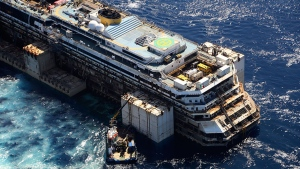 In this aerial picture provided by the Italian Civil Protection Department, the wreck of the Costa Concordia is towed by two tugboats as it leaves behind the tiny Tuscan island of Isola del Giglio, Italy, Wednesday, July 23, 2014. (AP / Courtesy of the Italian Civil Protection Department, ho)