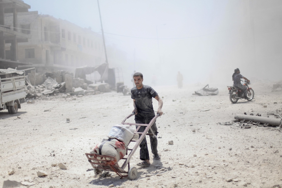 A Syrian man walks amid dust and rubble, aftermath of alleged barrel bomb attack by Assad regime forces on local civilians in the Qadi Askar neighbourhood in Aleppo, Syria, on July 8, 2014. (Ahmed Deeb/REX)
