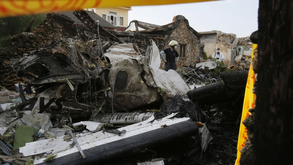 An emergency worker surveys the wreckage of crashed TransAsia Airways flight GE222 on the outlying island of Penghu, Taiwan, Thursday, July 24, 2014. (AP / Wally Santana)