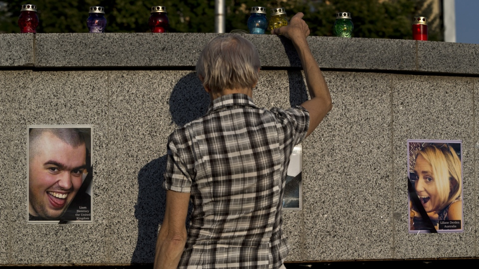 A woman places a candle backdropped by pictures of victims of the MH17 air crash during a memorial concert in Kharkiv, Ukraine, Thursday, July 24, 2014. (AP / Vadim Ghirda)