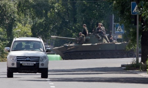 Pro-Russian fighters ride a airborne self-propelled artillery gun Nona in downtown Donetsk, eastern Ukraine on Thursday, July 24, 2014. (AP / Dmitry Lovetsky)