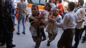 Palestinian medics run carrying children, wounded in an Israeli strike on a compound housing a U.N. school in Beit Hanoun, in the northern Gaza Strip, into the emergency room of the Kamal Adwan hospital in Beit Lahiya, Thursday, July 24, 2014. (AP / Majed Hamdan)