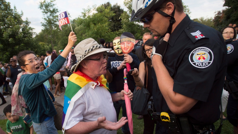 An LGBTQ protestor speaks to a police officer at Ford Fest in Toronto on Friday, July 25, 2014. (Darren Calabrese / THE CANADIAN PRESS)